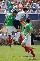 Juan Carlos Valenzuela (21) of Mexico (MEX) and Brian Ching (11) of the United States (USA) go up for a header. Mexico (MEX) defeated the United States (USA) 5-0 during the finals of the CONCACAF Gold Cup at Giants Stadium in East Rutherford, NJ, on July 26, 2009.