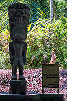"""A man stands behind the sign for the carved wooden tiki of Hawaiian god """"KU"""" at the Hawai'i Tropical Botanical Garden in Onomea (near Hilo), Big Island of Hawai'i."""