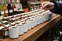 London, UK. 15.11.2014. A customer samples chutneys and sauces on a stall at Borough Market. Photograph © Jane Hobson.
