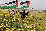 Palestinian men hold up the national flag as he walks across a field during a rally marking Land Day in Beit Hanun in the northern Gaza Strip close to the border with Israel on March 31, 2013. The annual demonstrations mark the deaths of six Arab Israeli protesters at the hands of Israeli police and troops during mass protests in 1976 against plans to confiscate Arab land in the northern Galilee region. Photo by Ashraf Amra