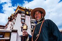 A Tibetan pilgrim spins a prayer wheel outside the Potala Palace (former residence of the Dalai Lama), Lhasa, Tibet, China.