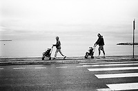 France. Alpes-Maritimes department. Cannes. A couple walks on the side walk and both parents push a stroller with a child.  Mediterranean Sea. 2.11.02 © 2002 Didier Ruef