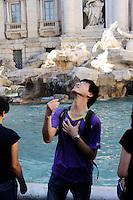 Roma 2 Agosto 2010.Turista getta la monetina  dentro Fontana di Trevi.Rome August 2, 2010.Tourist  throws  coins into the Trevi Fountain