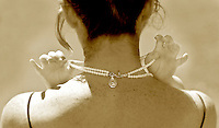 A pair of young hands grasp a string of pearls around a womans neck during a wedding. (Photo by Scott Eklund/Red Box Pictures)