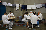 Inmates play cards next their drying laundry in crowded gymnasiums coverted into dormitories at the California State Prison &ETH; Sacramento in Folsom, California, Thursday, Dec. 7, 2006. The California prison system is so crowded that 16,000 inmates are assigned cots in hallways and gyms &ETH; leading Gov. Arnold Schwarzenegger to declare a state of emergency for the system.