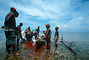 Obet, a shark caller from Kontu village on the West Coast of New Ireland is surrounded by excited children after bringing in a shark he caught on his outrigger canoe..Kontu, New Ireland Province, Papua New Guinea;