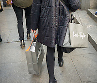 A shopper laden with her Lord & Taylor purchases in New York on Sunday, November 20, 2016. As shoppers turn to online shopping and stores expand their opening hours into Thanksgiving fewer shoppers flocking to the stores on Friday. (© Richard B. Levine)