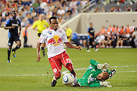 Dane Richards (19) of the New York Red Bulls goes down under pressure from San Jose Earthquakes goalkeeper Jon Busch (18) during a Major League Soccer (MLS) match at Red Bull Arena in Harrison, NJ, on August 28, 2010.