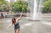 New Yorkers and visitors enjoy the fountain in Washington Square Park in Greenwich Village in New York on Monday, July 25, 2016. Temperatures are expected to be in the 90's F with excessive humidity breaking for thunderstorms in the late afternoon. The city has issued a heat advisory with cooling centers throughout the five boroughs. ( © Richard B. Levine)