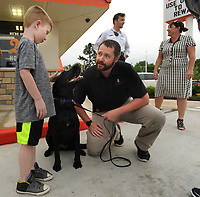 NWA Democrat-Gazette/ANDY SHUPE<br /> Braxton Glisson (left), 6, of Fayetteville pets Oakley, a K-9 officer with the University of Arkansas Police Department, as her handler, officer Joe Copelin, answers questions Thursday, April 20, 2017, during an evening of fundraising for the department's K-9 division at Whataburger on Martin Luther King Jr. Boulevard in Fayetteville. The department is raising money to support the K-9 division including the purchase of a new Handler Protection Training suit for training.