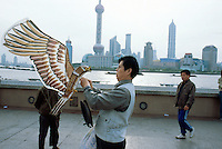 """China. Shanghai. Downtown. City center.  Early morning, a chinese man flies an eagle kite. Pudong skyline seen from """"The Bund"""". Over 1 and 1/2 times larger than urban Shanghai itself, the Pudong new area consists of the entire eastern bank of the Huangpu river. Pudong is the new area of development where the growing business needs constantly new modern high buildings, real """"skyscrapers"""". Pudong has become Shanghai and China's economic powerhouse.The Bund is the most impressive 2 km in Shanghai. © 2002 Didier Ruef"""