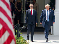United States President Donald J. Trump walks to the US Treasury Building with US Secretary of the Treasury Steven Mnuchin to sign Executive Orders concerning financial services in Washington, DC on April 21, 2017.<br /> Credit: Ron Sachs / Pool via CNP /MediaPunch