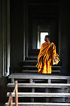A young Buddhist monk walks through a temple at Angkor Wat, Cambodia. June 9, 2013.