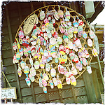 Photo shows miniature woven sandals  hanging outside a store in the old post town known as Ouchijuku in the Aizu region of Fukushima Prefecture, Japan.  Photographer: Rob Gilhooly