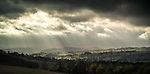 Crepuscular rays breaking through storm clouds over moors and mountains of the English Lake District
