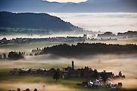 Autumn morning fog clears from village of Speiden and rural landscape of Allgaeu region, near Eisenberg, Bavaria, Germany