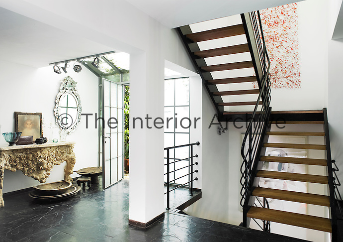 A spacious entrance hall with a tiled floor. A staircase with open treads leads to upper and lower floors.