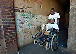 Blessing Manditsera gets help from his uncle, Huggins Here, exiting a condemned apartment building where they live, near the Mbare Market in Harare, Zimbabwe. Manditsera's legs were paralyzed when he suffered from tuberculosis, and he today uses a wheelchair provided by the Jairos Jiri Association with support from CBM-US.