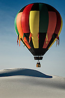 A lone hot air balloon suspended over the crest of a sand dune at White Sands National Monument.