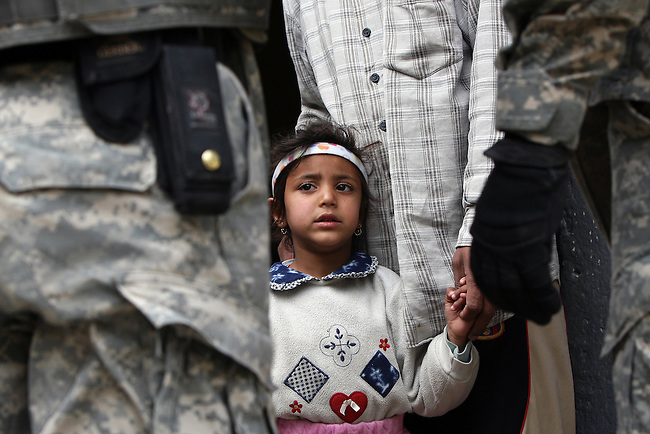 A little girl watches U.S. soldiers as they and Iraqi troops talk with her father  during a patrol in Mosul, Iraq. U.S. commanders say a string of new combat outposts and daily patrols by U.S. and Iraqi forces are pushing insurgents out of the city. March 1, 2008. DREW BROWN/STARS AND STRIPES