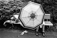 Switzerland. Zürich. A couple on a bench. The woman is  taking a nap and her man is seated behing an umbrella. © 1993 Didier Ruef