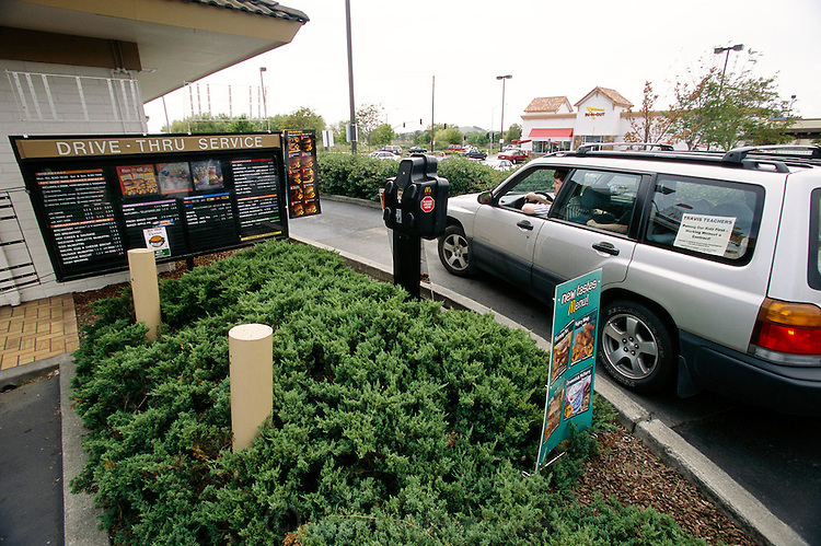 (MODEL RELEASED IMAGE). The Caven family stops at a McDonald's drive-thru in Napa, California, for Happy Meals on the way home from the weekly shopping expedition to Raley's, a California grocery chain. The high school where Craig teaches is on break this week, so the children are out of daycare and home with Dad. Hungry Planet: What the World Eats (p. 262).