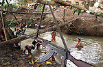 A gun hangs from a tree as FARC rebels bath in a river outside of San Vicente del Caguan in the former FARC controlled zone of Colombia. The FARC are Colombia's oldest and largest rebel group numbering over 18,000 rebels. (Photo/Scott Dalton)