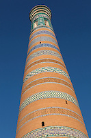 Low angle view of Islam Hodja Minaret, 1910,  Khiva, Uzbekistan, pictured on July 5, 2010, in the afternoon. Commissioned by the reforming Grand Visier, Islam Khodja, the minaret is 44.8 metres high, tapering towards the top, its ochre brick alternating with bands of decorative blue and white tiles. It is the final architectural achievement of the Khanates. Khiva, ancient and remote, is the most intact Silk Road city. Ichan Kala, its old town, was the first site in Uzbekistan to become a World Heritage Site(1991). Picture by Manuel Cohen.