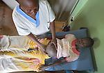 Marieta Carlo, a midwife, examines a pregnant woman's abdomen at the St. Daniel Comboni Catholic Hospital in Wau, South Sudan.