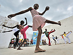 """Children practice capoeira on January 24, 2010, in a camp for homeless families in the Belair section of Port-au-Prince. The program, run by Viva Rio, a Brazilian nongovernmental organization, is designed to help children affected by the quake recover their emotional well-being. Under """"informed consent"""" rules that require prior approval, the photographer would have had to stop the girls from playing, go with them to find their parents, explain explain the intricacies of """"informed consent"""" and usage, get their signatures, then return to the community center to photograph the activity. That's a process that's allegedly designed to assure that the children are not depicted in an undignified manner. Photo by Paul Jeffrey."""