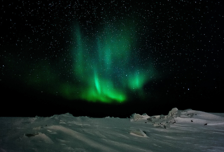 Bursts of greenish-blue color from the Northern Lights illuminate the night sky above the Great Slave Lake in Northwest Territories.