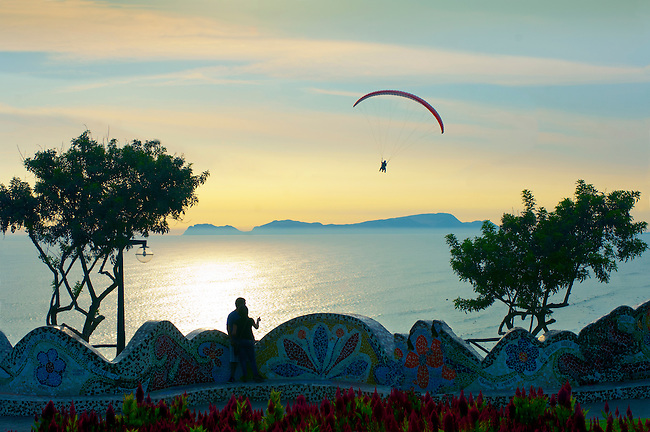 A couple in the Parque del Armor watch paragliders flying above the Pacific Ocean in Lima, Peru.