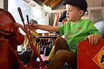 Joseph Willey, 4, of Los Gatos pulls the lever of a 1930's Allis Chalmers tractor on display at the Los Altos History Museum.