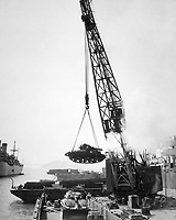 Marine Corps tanks - ready for the front lines - are swung aboard a barge at the Naval Supply Center by crane, for transhipment to our forces in the Pacific Far Eastern Command.  Oakland, CA, 1950.  Acme. (USIA)<br /> Exact Date Shot Unknown<br /> NARA FILE #:  306-PS-50-12226<br /> WAR &amp; CONFLICT BOOK #:  1403