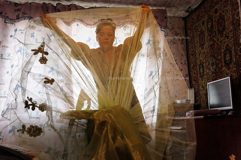 Hidden behind a sheer netting of the wedding dress, the bride Miroslava Osipova irons on her wedding day before the ceremony.