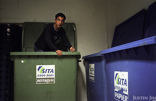 Dutch-Turkish teenager Hakan Dinc stands inside a rubbish container to crush paper packaging as part of his job at his uncle's grocery store in East Amsterdam..Dinc, 16, was born in the Netherlands. His grandparents from his father?s side came from Turkey in 1971, and his mother came in 1987. Dinc feels more Turkish than Dutch, most of his friends are Turkish and he wants to marry a Turkish girl. During his time off he works in his uncle?s grocery store. Later, he wants to have his own shop. Dinc is following a Commerce course at a vocational school in Amsterdam. .Dinc likes music, pool and chilling out. He has a fourteen-year-old sister and a brother aged ten months. .Picture shot in Amsterdam in 2004 by Justin Jin. .