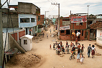 A small crowd gathers around a bateria drum corps as they practice a samba in the dirt streets of the Vigário Geral slum in Rio de Janeiro.