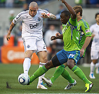 Vancouver Whitecaps FC  forward Eric Hassli takes a shot while Seattle Sounders FC defender Jhon Kennedy Hurtado  tries to block it during play at Qwest Field in Seattle Saturday June 11, 2011. The game ended in a 2-2 draw.