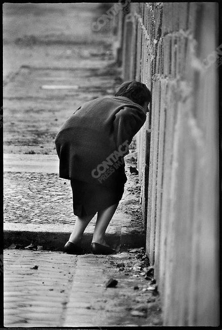 West Berliner looking into East Berlin through a crack in the Berlin Wall at the time of it's construction. West Berlin, Germany, November 1961