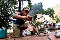 Jhón Jairo Morales, a Colombian street artist, creates a sculpture by melting down used plastic cups on the street of Cali, Colombia, 2 April 2004. Collecting and recycling of used plastic cups from the city dustbins allows him to create simple shaped plastic figures, usually animals. The original sculpture technique is based on melting down plastic in burner fire. Then he shapes fused plastic mechanically and gives the material a design. The artistic process is closed by sinking a figure into the cold water. The artist works and sells his sculptures in the Metropolitan Park of Cali.
