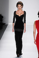 Model walks runway in a black silk velvet starlet gown w/silk chiffon garter insert+sleeves and satin pipping, from the Zang Toi Fall 2012 &quot;Glamour At Gstaad&quot; collection, during Mercedes-Benz Fashion Week New York Fall 2012 at Lincoln Center.