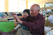 May 18, 2011; Minamisanriku, Miyagi Pref., Japan - Kuniko (L) and Toyotaro Suzuki sit in their living area at the Shizukawa High School Evacuation Center in Minamisanriku. ..There home was completely destroyed but all their family members survived the magnitude 9.0 Great East Japan Earthquake and Tsunami that devastated the Tohoku region of Japan on March 11, 2011.