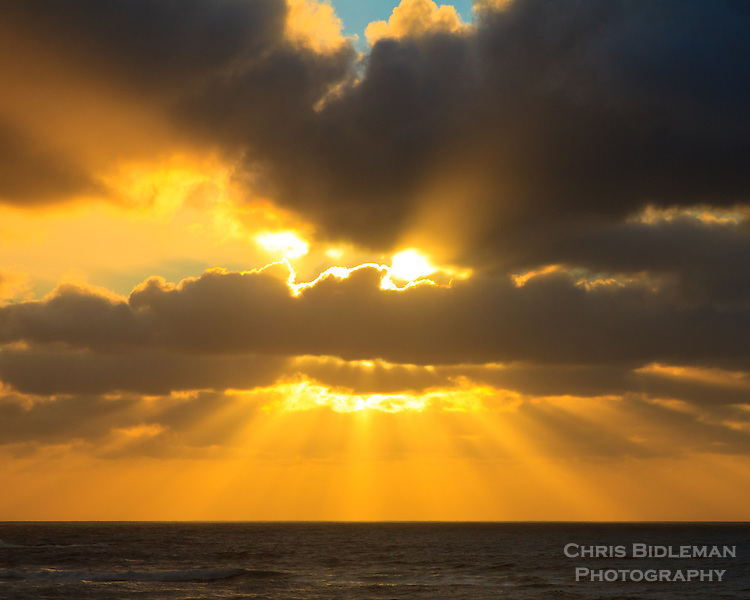Rays of sunlight are shining through clouds over the ocean at sunset along the Oregon Coast