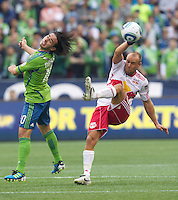 Seattle Sounders FC midfielder Mauro Rosales and New York Red Bulls midfielder Joel Lindpere battle for the ball during play at Qwest Field in Seattle Saturday June 23, 2011. The Sounders won the game 4-2.