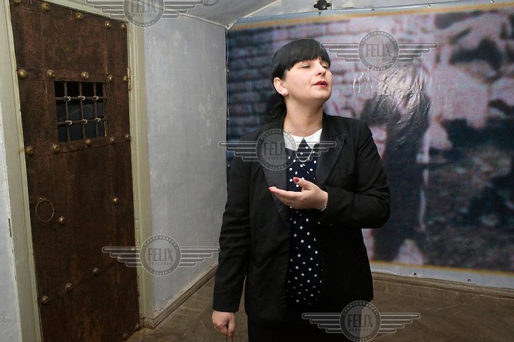 A guide shows to visitors a replica Soviet era interogation room in the Stalin Museum.
