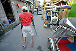 Florencio Fajardo, president of the local organization of people living with disabilities in Orani, a seaside town in the Philippines province of Bataan, walks along a street in his heighborhood.