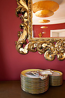A pendant lamp is reflected in one of several antique gilt-framed mirrors which decorate the walls of the circular dining room