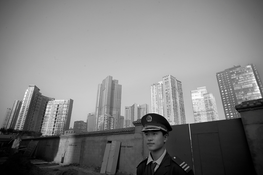 A Private security guard watches over the entrance of a construction site in Beijing's Chaoyang business district.