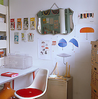 Home office with various packaging and drawings displayed on the wall for inspiration