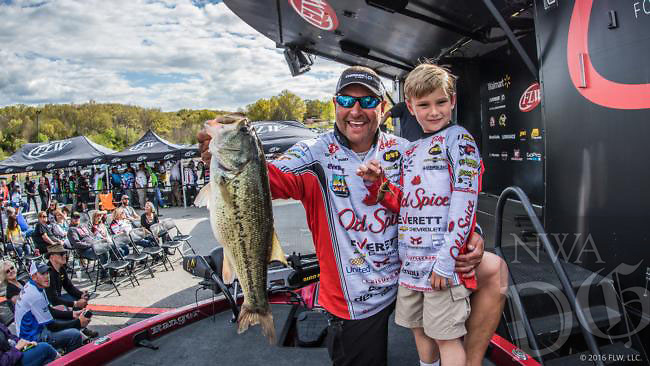 Courtesy photo<br /> Greg Bohannan of Bentonville, with his son, Brock,  weighs a largemouth bass at the Walmart FLW Tour event at Beaver Lake last April. He will fish in his fourth FLW championship, the Forrest Wood Cup, at Lake Wheeler in Alabama.